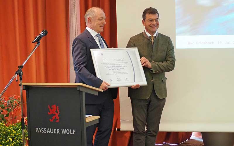 IHK-Präsident Thomas Leebmann übergibt die Ehrenurkunde an Florian Leebmann, den geschäftsführenden Gesellschafter des Passauer Wolf. Bildnachweis:  PASSAUER WOLF/Stefanie Kreß