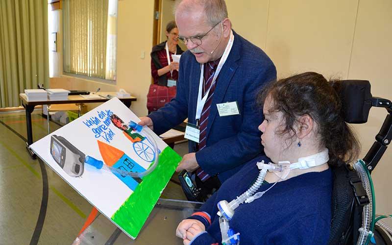 """Dr. Paul Diesener bekommt von seiner ehemaligen Patientin Amelie ein selbst gemaltes und gestaltetes Bild. Darauf steht: """"ich bin ein ganz normales Kind"""". Auf dem Bild hat Amelie ihre erste Trachealkanüle verarbeitet. Bild: Jagode"""